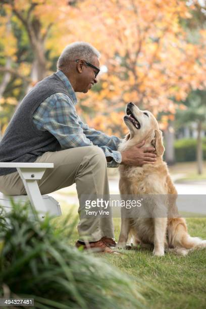 African American man petting dog outdoors