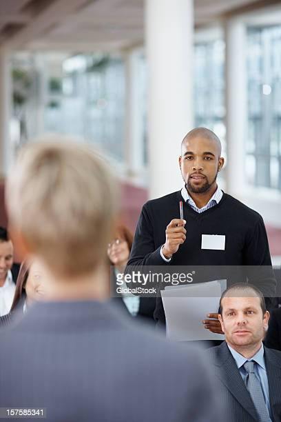African American man questioning a speaker while at seminar