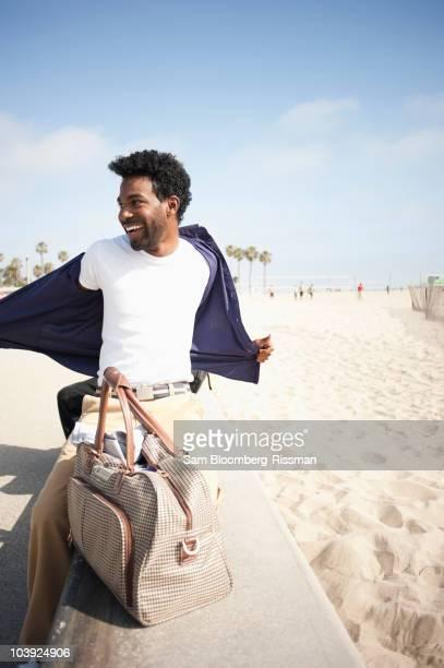 African American man removing shirt at beach