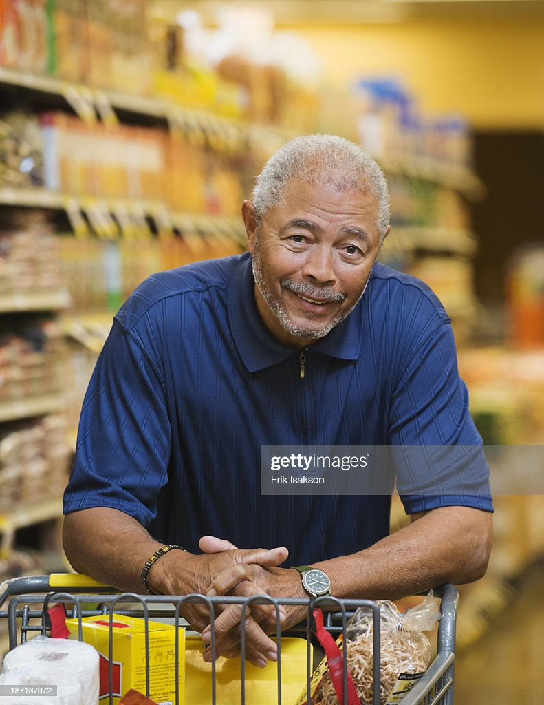 African American man smiling in grocery store : Stock Photo