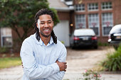 African American man (20s) standing in front of house.