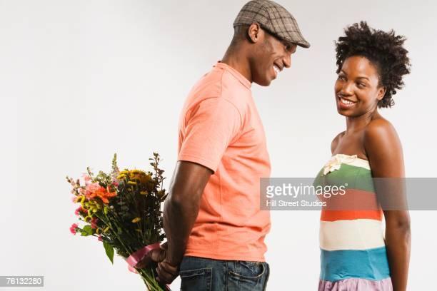 African American man surprising girlfriend with flowers