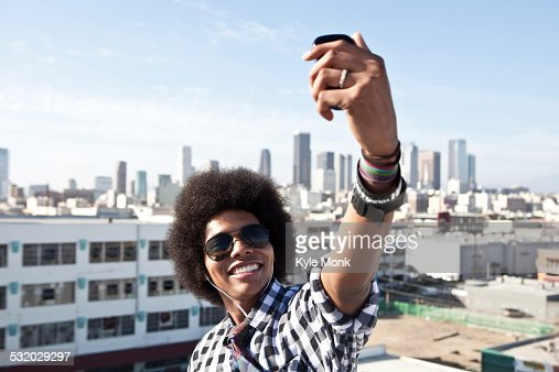 African American man taking cell phone picture from urban rooftop