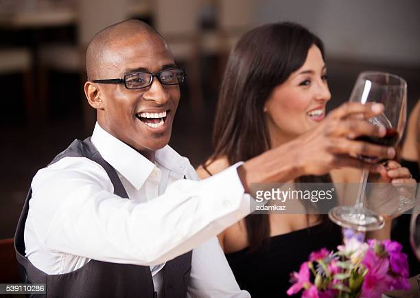 African American Man Toasting at Nice Dinner wtih Friends