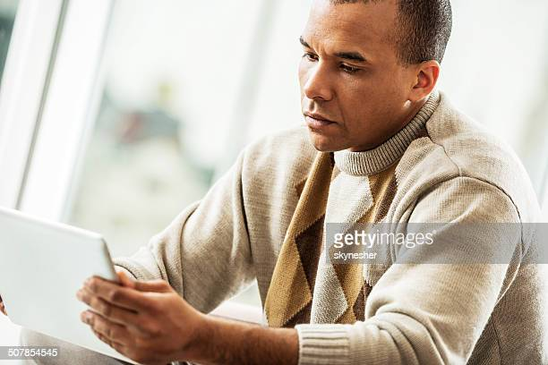 African American man using digital tablet.