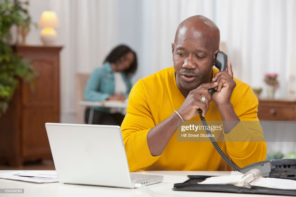 African American man using laptop and talking on telephone