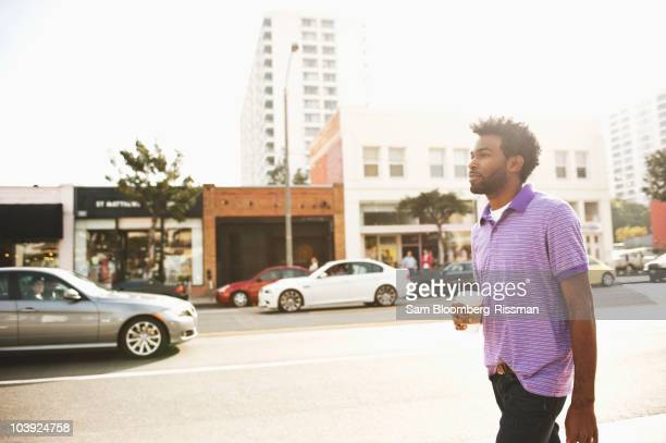African American man with coffee cup walking on sidewalk