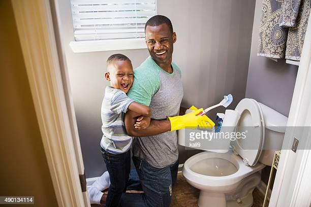 African American man with son, cleaning bathroom toilet