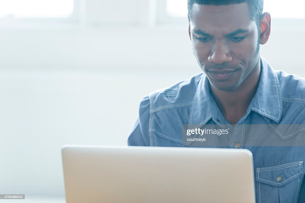 African American man working on a laptop computer. : Stock Photo