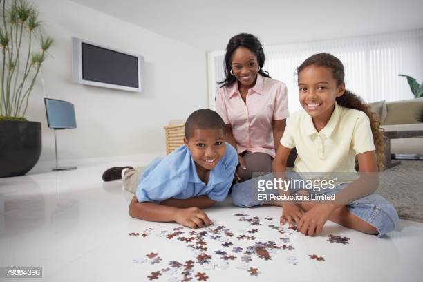 African American mother and children playing with puzzle