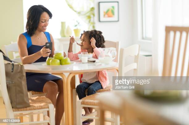 African American mother and daughter at breakfast table