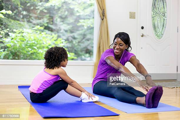 African American mother and daughter doing yoga in a studio