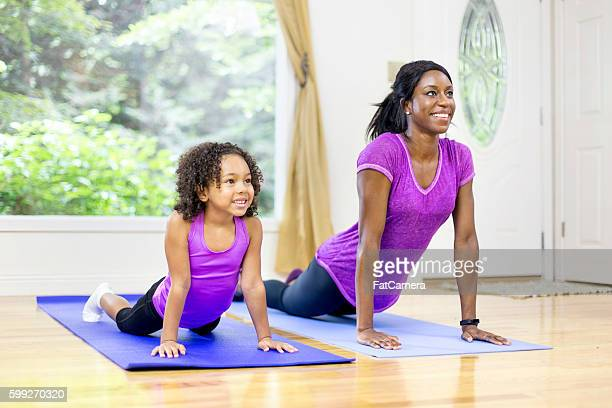 African american mother and daughter doing yoga