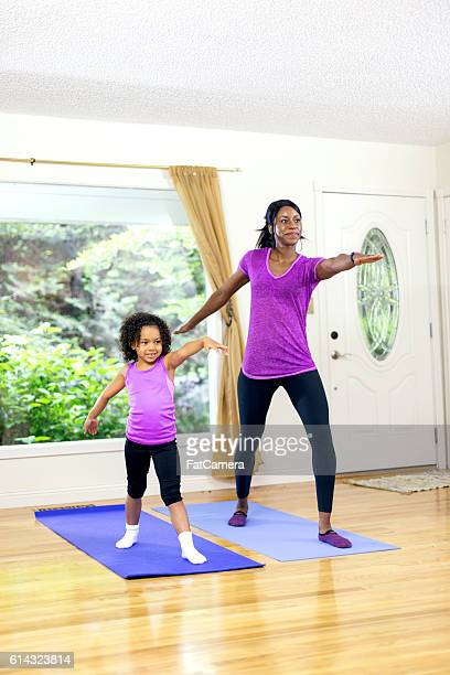 African American mother and daughter doing yoga together