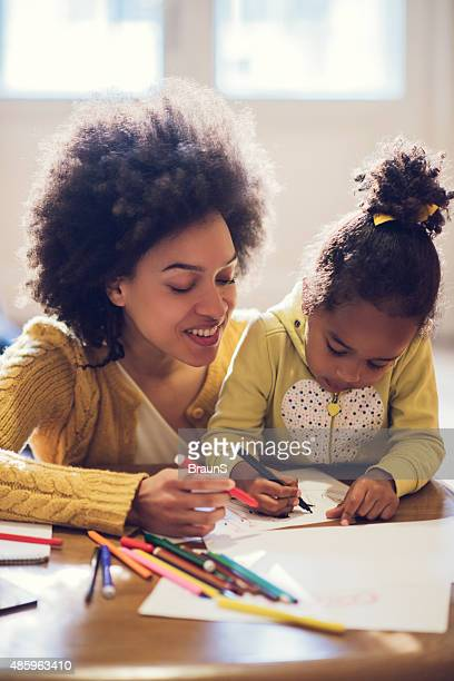 African American mother and daughter enjoying while coloring tog