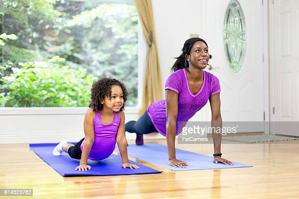 African American mother and daughter holding a yoga pose