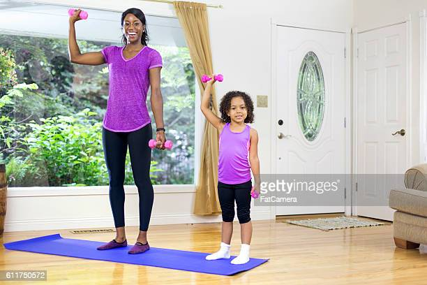 African American mother and daughter lifting weights together
