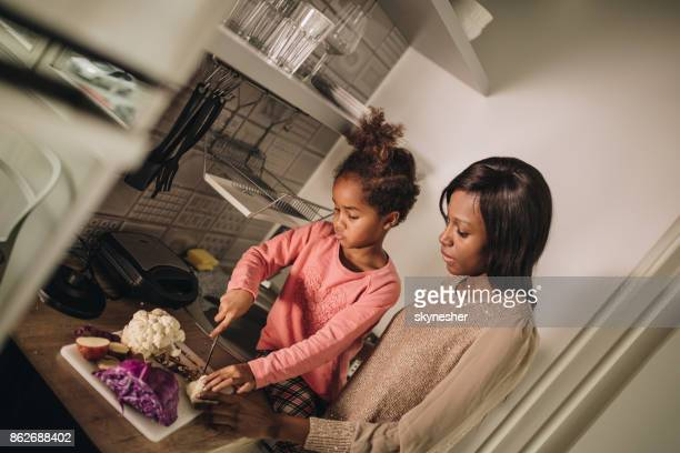 African American mother and daughter preparing food in the kitchen.