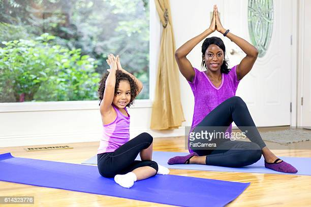 African American mother and daughter sitting on yoga mats