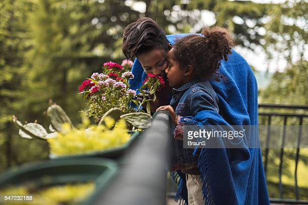African American mother and daughter smelling flowers on a terrace.