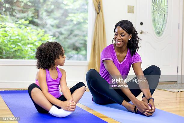 African American mother and daughter stretching before yoga