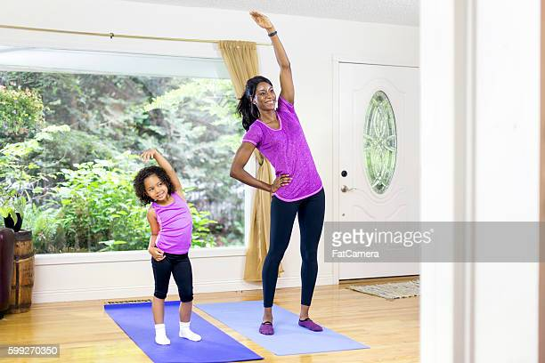 African american mother and daughter stretching
