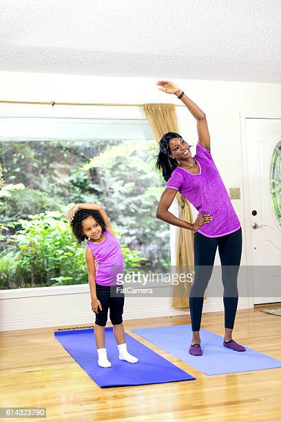 African American mother and daughter stretching to one side