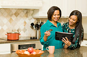 African American mother and daughter using digital tablet