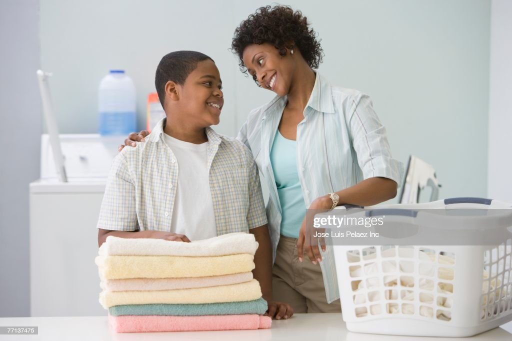 African American mother and son doing laundry : Stock Photo