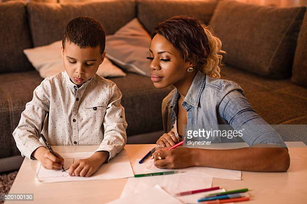 African American mother and son drawing at home.