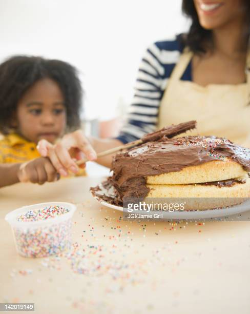 African American mother and son icing cake