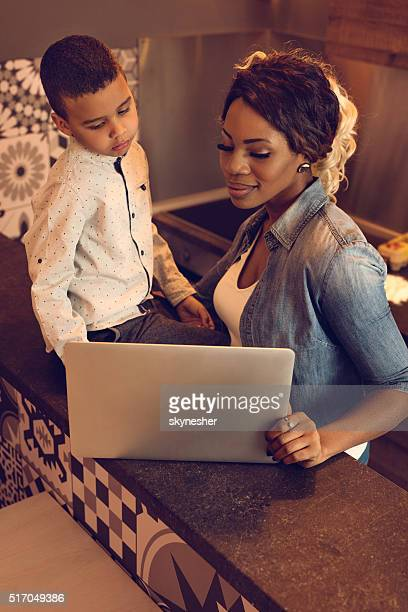 African American mother and son using laptop together.