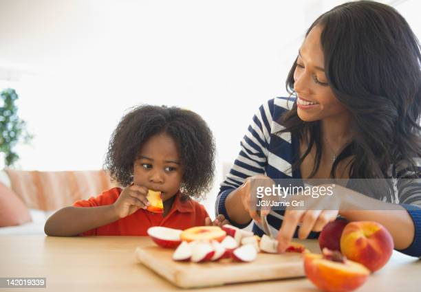 African American mother cutting fruit for son