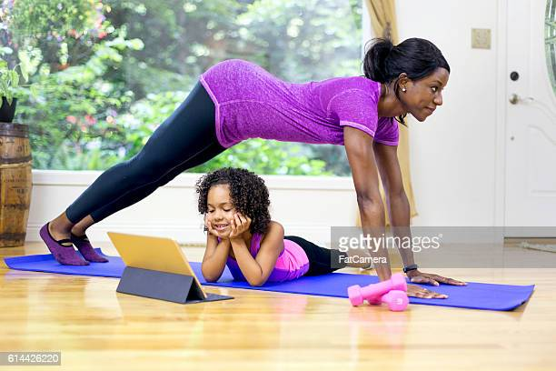 African American mother doing yoga with her daughter