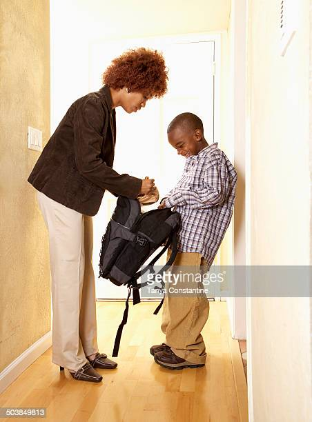 African American mother getting son ready for school