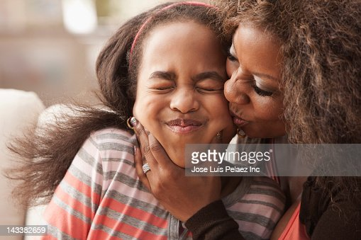 African American mother kissing daughter : Stock Photo