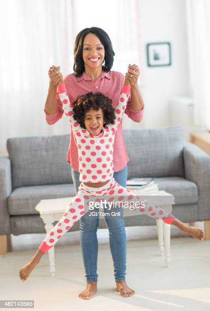 African American mother lifting daughter playfully