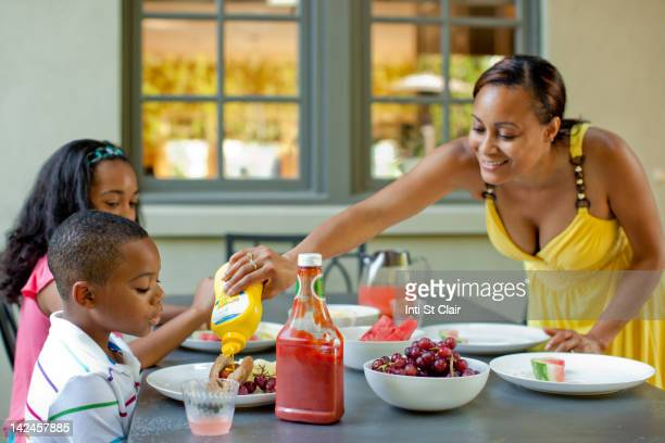 African American mother preparing lunch for children