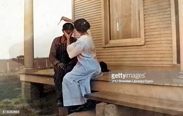 African American mother sitting with her child on the front porch of a plantation style home using a straight razor to cut the childs hair holding...