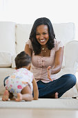 African American mother watching baby crawl