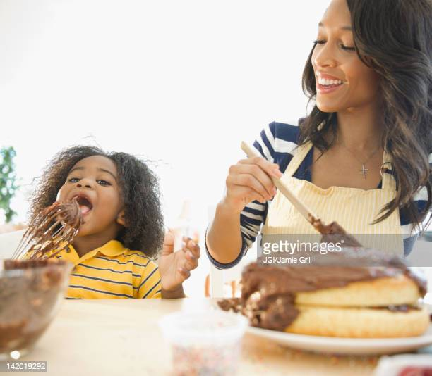 African American mother watching son licking cake icing