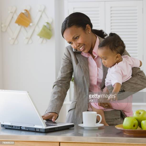 African American mother working at holding baby