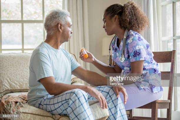 African American nurse giving patient medication