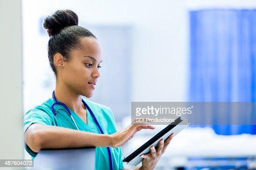 African American nurse or doctor using digital tablet in hospital