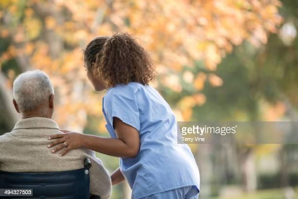 African American nurse pushing patient in wheelchair