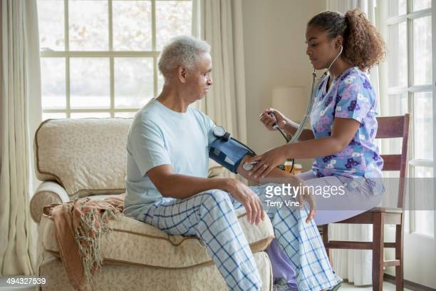 African American nurse taking patient's blood pressure