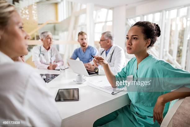 Infirmière afro-américain parlant à son collègue sur une réunion.