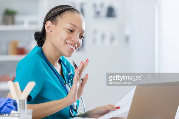 African American nurse waves while video chatting with colleague