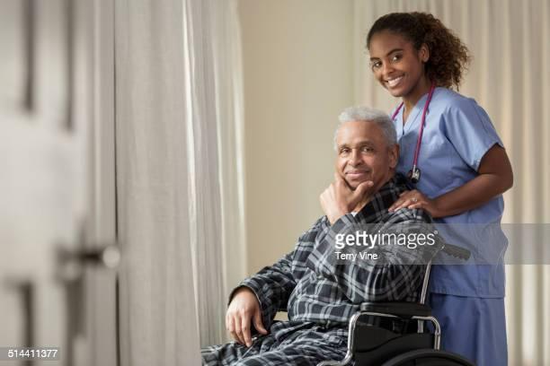 African American nurse wheeling Senior patient