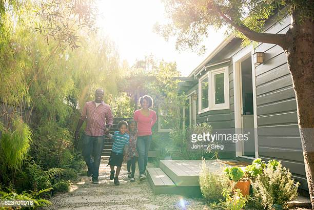 African American parents with two children walking in garden